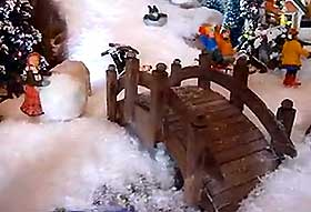 View of a model bridge spanning a frozen village stream