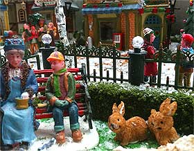 Picture of homemade miniature hedge, next to the Lemax figurines named Feeding the Birds