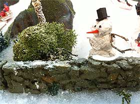 Image of snowman with green reindeer moss