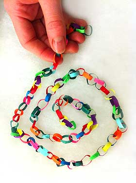 Photograph of a festive model paper chain, pictured with hand to show scale of the decoration