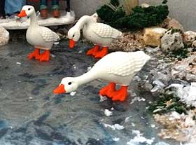 Close-up picture of model Playmobil geese on an icy pond made from PVA glue