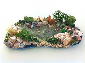 Image of a small frozen model pond, with miniature ducks, rabbits and a tiny frog