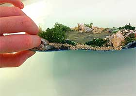 Side-view image of a small model pond, made with PVA glue and semi-rigid plastic