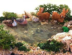 Image of miniature geese and rabbits, sitting on the edge of the icy water