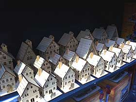 Photograph of cheap wooden village houses being sold at Christmas time
