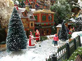 Photo showing Mr and Mrs Claus outside the Lemax model building named Michelle's Village Bakery