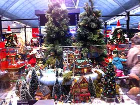 Photo of a Christmas Village display at a garden centre, with out of scale trees used in the background