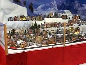 Image of an official Christmas Village display, using red velvet to create a neat, formal front to the panorama