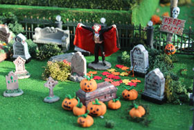 Photo of steps and a pumpkin head man in a model Halloween village